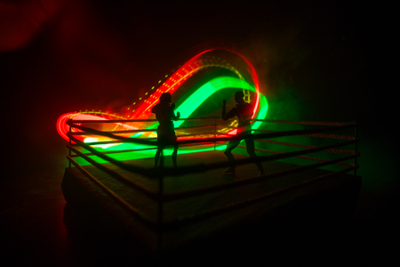 Man and woman boxing on the ring. Sport concept. Artwork decoration with toys on foggy toned dark background.
