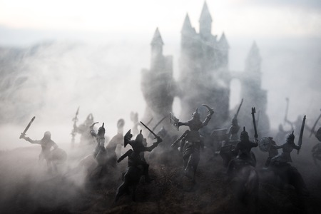 Medieval battle scene with cavalry and infantry. Silhouettes of figures as separate objects, fight between warriors on sunset foggy background. Selective focus Archivio Fotografico