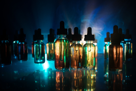 Vape concept. Smoke clouds and vape liquid bottles on dark background. Light effects. Useful as background or electronic cigarette advertisement. Selective focus