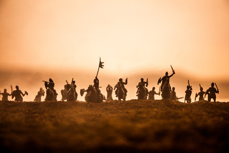 Medieval battle scene with cavalry and infantry. Silhouettes of figures as separate objects, fight between warriors on sunset foggy background. Selective focus 版權商用圖片