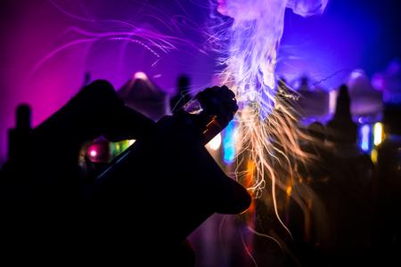 Concetto di vaporizzazione. Esplosione di sigaretta elettronica vape. Nuvole di fumo e bottiglie di liquido vape su sfondo scuro. Effetti di luce. Utile come pubblicità per lo svapo. Messa a fuoco selettiva Archivio Fotografico