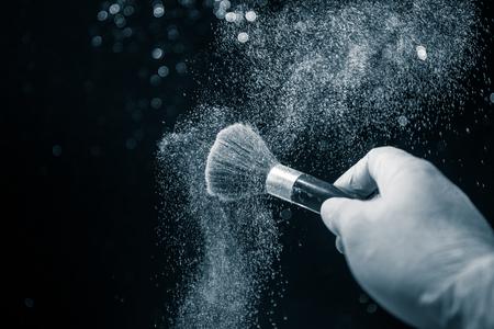 Pincel de maquillaje en mano con polvo cosmético sobre fondo oscuro con luz y humo. Salpicaduras de polvo en la oscuridad. Enfoque selectivo