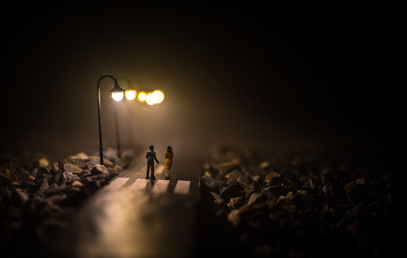 Artwork decoration. Silhouette of couple walking under street lights in night. Peaceful atmosphere in mist. Foggy air. Love concept. Selective focus