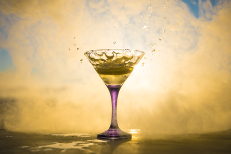 Martini cocktail glass splashing on foggy sunset background or colorful cocktail in glass with splashes and lemon. Outdoor open air party entertainment. Selective focus