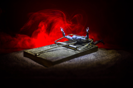 Kreatives Konzept. Kunstwerk Dekoration der Mausefalle im Sand auf dunkel getönten nebligen Hintergrund. Mausefalle hat einen Mann gefangen. Selektiver Fokus