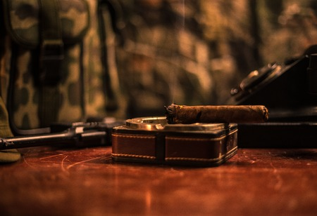 Close up of a Cuban cigar and ashtray on the wooden table. Communist dictator commander table in dark room. Army general`s work table concept. Artwork decoration Stockfoto