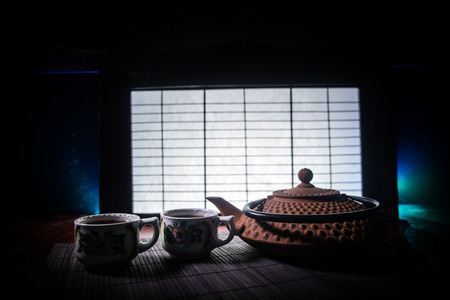 Tea concept. Japanese tea ceremony culture east beverage. Teapot and cups on table with bamboo and tradicional Japan ornament decor elements
