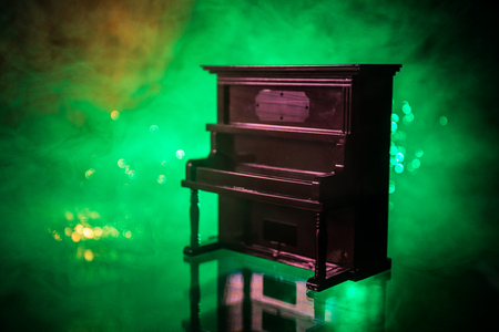 Creative concept. Artwork decoration with piano on dark toned foggy background with light. Selective focus