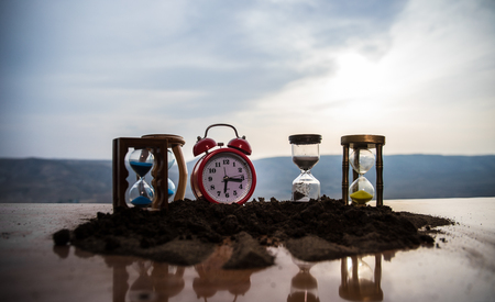 Hourglasses and red alarm clock during sunset. Time concept. Selective focus.