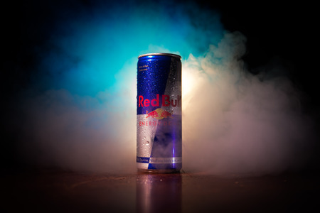 BAKU, AZERBAIJAN - April 20, 2018: Red Bull classic 250 ml can on dark toned foggy background. Red Bull is an energy drink sold by Austrian company Red Bull GmbH