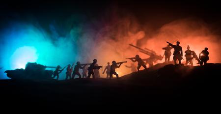 Concetto di guerra. Sagome militari che combattono la scena sullo sfondo del cielo di nebbia di guerra, la sagoma dei soldati della guerra mondiale sotto lo skyline nuvoloso di notte. Archivio Fotografico