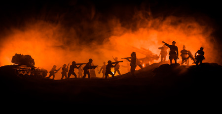 War Concept. Military silhouettes fighting scene on war fog sky background, World War Soldiers Silhouette Below Cloudy Skyline At night.