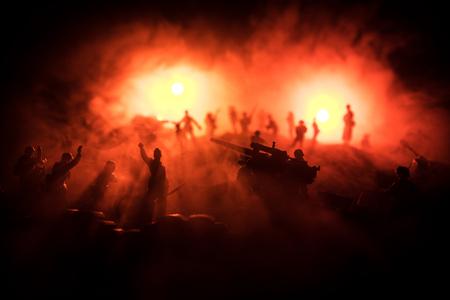 Notion de guerre. Scène de combat de silhouettes militaires sur fond de ciel de brouillard de guerre, silhouette de soldats de la guerre mondiale sous l'horizon nuageux la nuit.