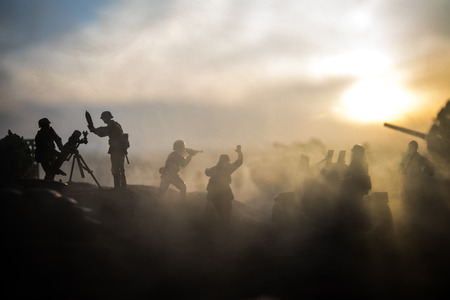 War Concept. Military silhouettes fighting scene on war fog sky background, World War Soldiers Silhouette Below Cloudy Skyline at sunset.