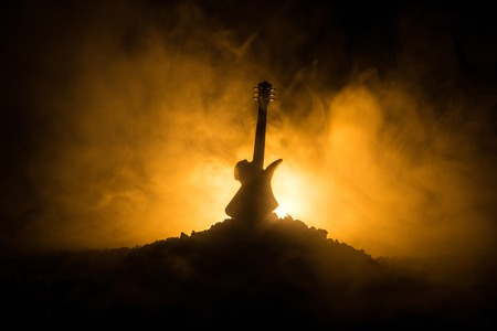 Music concept. Acoustic guitar on a dark background under beam of light with smoke. Emptry space for text. Fire effects. Surreal guitar 写真素材