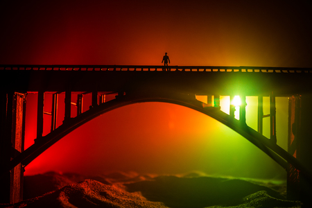 Artwork decoration. Silhouette of powerful metallic bridge at night with foggy backlight. Silhouette of person standing on bridge. Selective focus