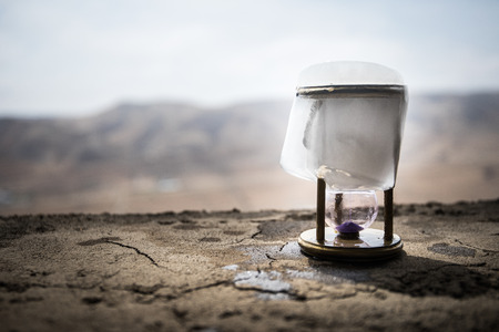 A concept of frozen time. Hourglass in ice. Creative artwork decoration. Selective focus