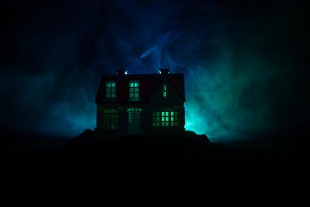Vieille maison avec un fantôme dans la forêt la nuit ou Abandoned Haunted Horror House dans le brouillard. Ancien bâtiment mystique dans la forêt d'arbres morts. Arbres la nuit avec la lune. Lumières surréalistes. Concept d'Horreur Halloween Banque d'images