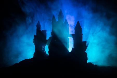 Altes Haus mit einem Geist im Wald bei Nacht oder verlassenes Spukhorrorhaus im Nebel. Altes mystisches Gebäude im toten Baumwald. Bäume in der Nacht mit Mond. Surreale Lichter. Horror Halloween Konzept Standard-Bild