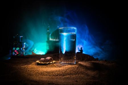 Agua y dátiles. Iftar es la cena. Vista de la decoración de vacaciones de Ramadán Kareem en la arena. Tarjeta de felicitación festiva, invitación a la fiesta musulmana. Enfoque selectivo