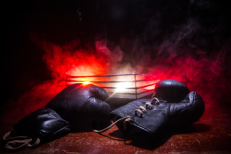 Empty boxing ring with red ropes for match in the stadium arena. Boxing gloves ready to fight. Empty space for text. Foggy background with light. Selective focus