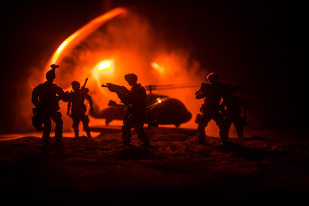 Artwork decoration. Soldiers in the desert during the military operation with combat helicopter or Helicopter assault special forces. Selective focus Stock Photo