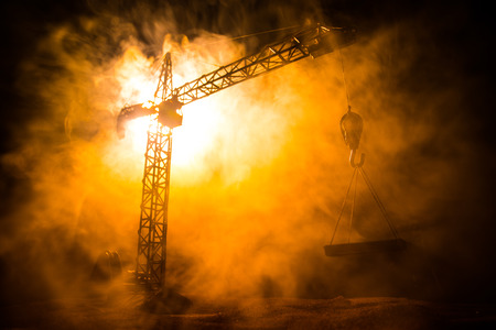 Abstract Industrial background with construction crane silhouette over amazing night sky with fog and backlight. Tower crane against the foggy sky at night. Industrial skyline. Selective focus Imagens
