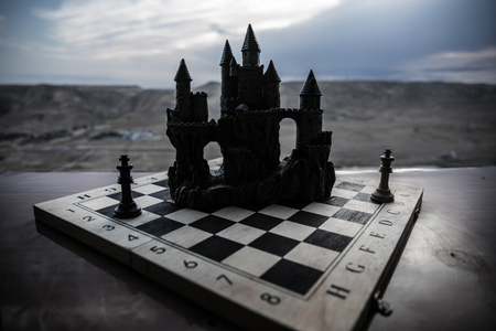 Chess board game concept of business ideas and competition. Chess figures and old medieval castle on a chessboard. Outdoor sunset background. Selective focus