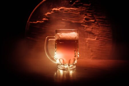 Creative concept. Single beer glass on wooden table at dark toned foggy background. Selective focus