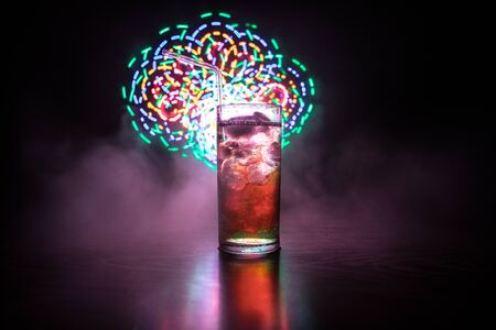 Cocktail glass splashing on dark toned smoky background or colorful cocktail in glass. Party club entertainment. Mixed light. Selective focus