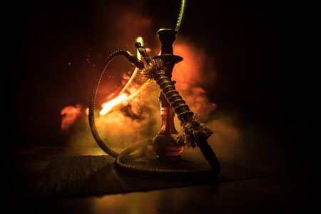 Hookah hot coals on shisha bowl on dark foggy background. Stylish oriental shisha. Creative concept 版權商用圖片