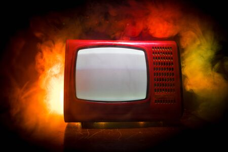 Old vintage red TV with white noise on dark toned foggy background. Retro old Television reciever no signal. Selective focus