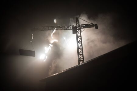Abstract Industrial background with construction crane silhouette over amazing night sky with fog and backlight. Tower crane against the foggy sky at night. Industrial skyline. Selective focus 스톡 콘텐츠