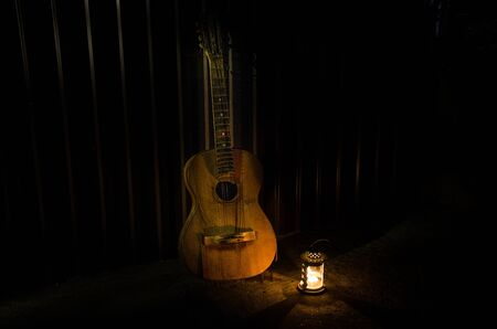 An wooden acoustic guitar is against a grunge textured wall. The room is dark with a spotlight for your copyspace. old broken guitar