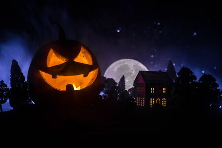 Horror view of Halloween pumpkin with scary smiling face. Head jack lantern with haunted building and tree on dark toned foggy background. 스톡 콘텐츠