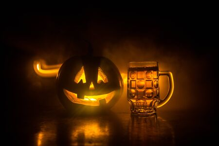 Glass of cold light beer with pumpkin on a wooden table for Halloween. Glass of fresh beer and pumpkin on a dark toned foggy background