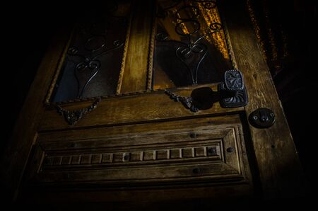 Close up view of old antique wooden door inside a dark room. Selective focus. Horror concept