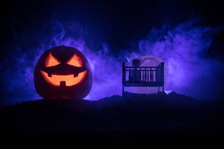 Horror Halloween concept. Old creepy eerie wooden baby crib and scary smiling glowing pumpkin in dark toned foggy background. Selective focus Banco de Imagens
