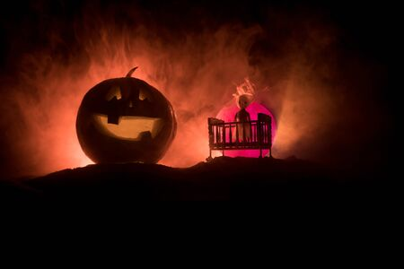 Horror Halloween concept. Old creepy eerie wooden baby crib and scary smiling glowing pumpkin in dark toned foggy background. Selective focus Imagens