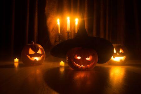 Halloween pumpkin head jack o lantern with glowing candles on background. Pumpkins on wooden floor. Selective focus Фото со стока