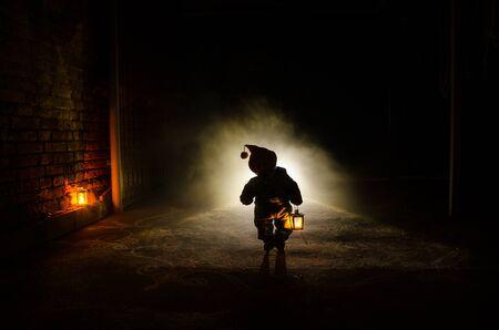 Escena de terror del fantasma de un niño aterrador, silueta de muñeca aterradora sobre fondo oscuro brumoso con luz. Concepto de Halloween de terror