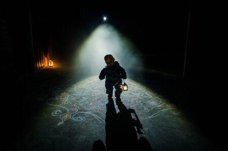 Horrorszene eines gruseligen Kindergeistes, Silhouette einer gruseligen Babypuppe auf dunklem nebligen Hintergrund mit Licht. Horror-Halloween-Konzept Standard-Bild