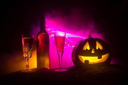 Tema della festa del vino di Halloween. Due bicchieri di vino e bottiglia con Halloween - vecchio jack-o-lantern su sfondo nebbioso dai toni scuri. Zucca di Halloween spaventosa