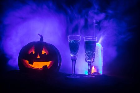 Halloween wine party theme. Two glasses of wine and bottle with Halloween - old jack-o-lantern on dark toned foggy background. Scary Halloween pumpkin