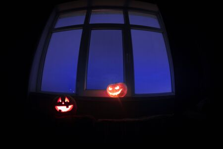 Scary Halloween pumpkin in the mystical house window at night or halloween pumpkin in night on room with blue window. Symbol of halloween in window. Selective focus