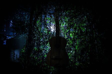 An wooden acoustic guitar at night. with spotlight for your copyspace. old broken guitar
