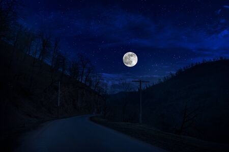 Mountain Road through the forest on a full moon night. Scenic night landscape of country road at night Stock Photo