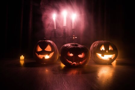 Halloween pumpkin head jack o lantern with glowing candles on background. Pumpkins on wooden floor. Selective focus 스톡 콘텐츠