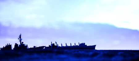 Military navy ships in a sea bay at sunset time. Artwork table decoration. Selective focus