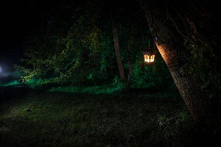 Horror Halloween Konzept. Brennende alte Öllampe im Wald bei Nacht. Nachtlandschaft einer Alptraumszene. Selektiver Fokus.